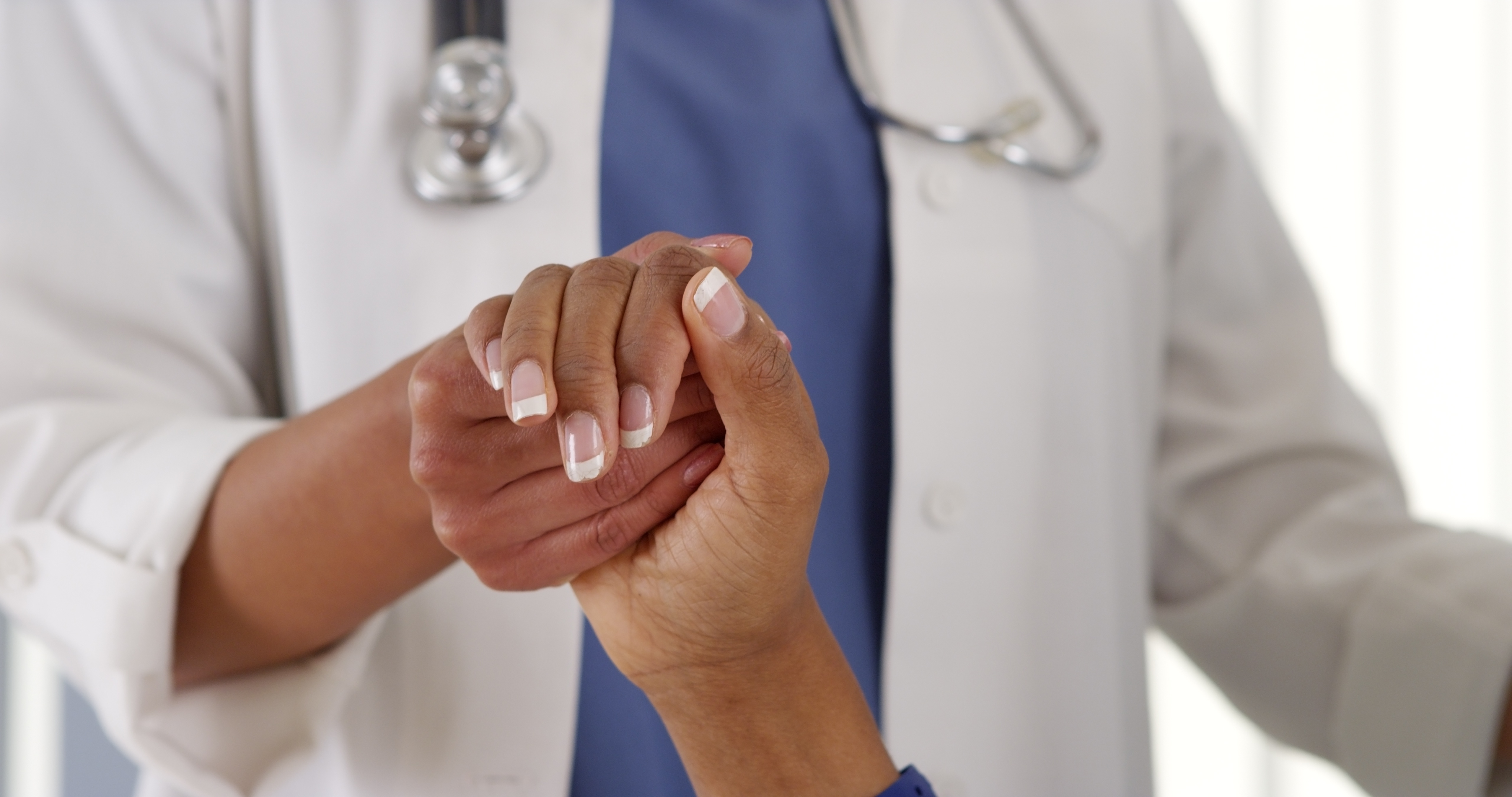 Doctor_holding_the_hand_of_a_patient.jpeg
