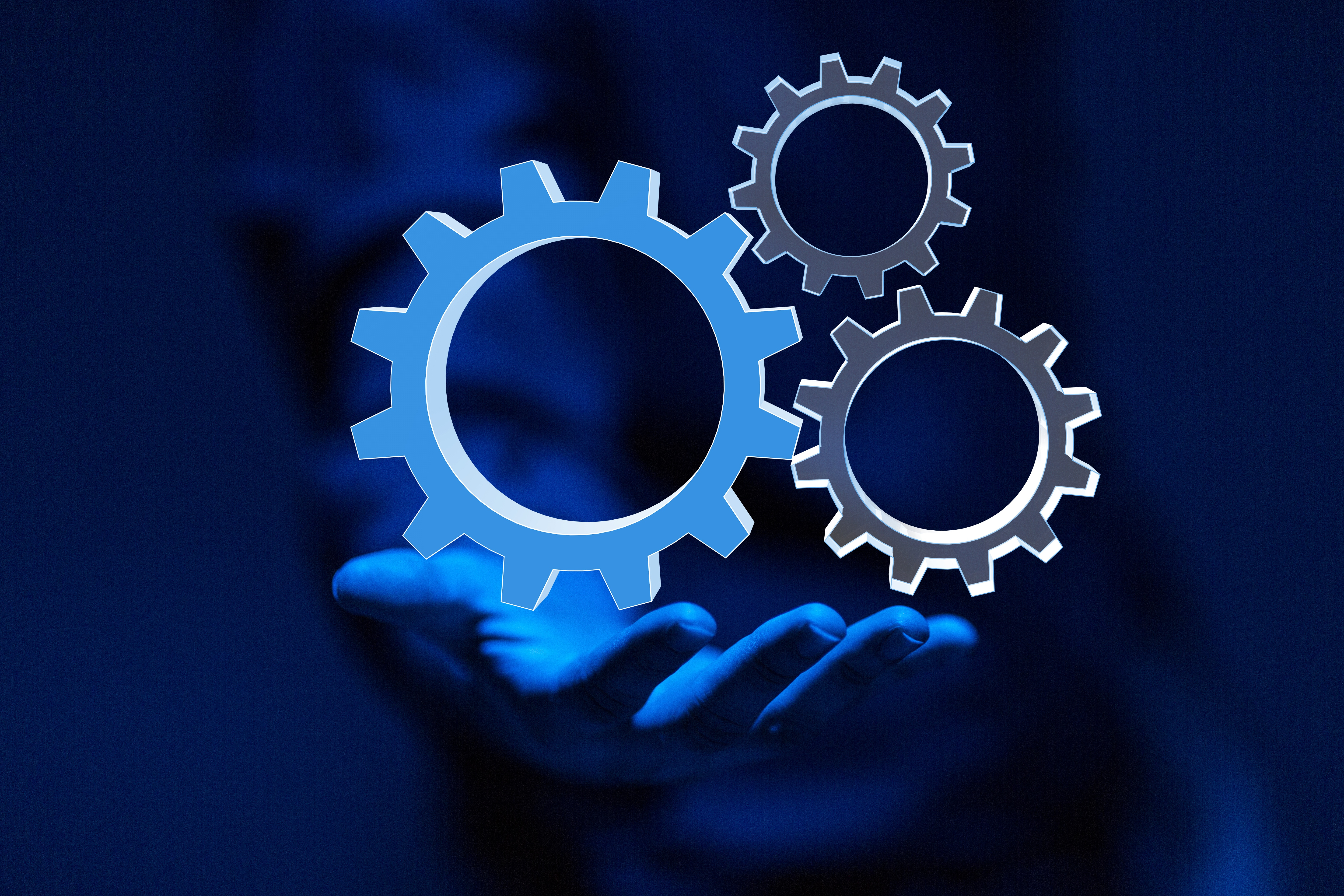 Image of gears hovering over an outstreahced hand.
